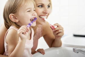 Family brushing teeth side-by-side