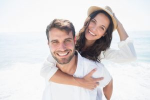 couple smiling on the beach after visiting their cosmetic dentist